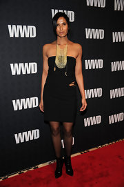 Padma Lakshmi paire her strapless black dress with matching pointy-toe ankle boots. She wore the boots over sheer black tights.