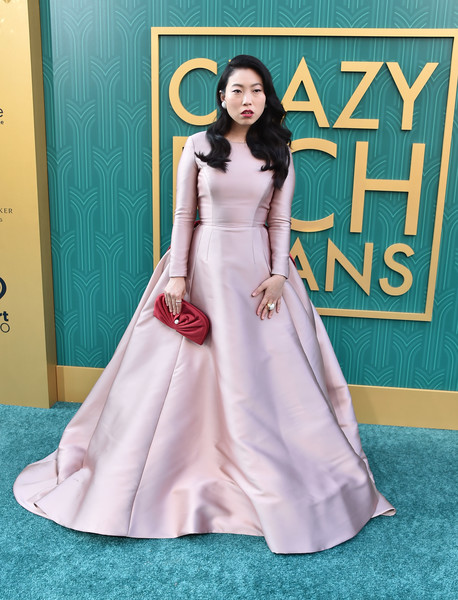 Awkwafina polished off her look with a red satin clutch by Jimmy Choo.