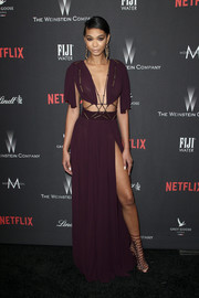 Chanel Iman attended the Weinstein Company Golden Globes party wearing a midriff-baring plum-colored gown held together by metallic straps.