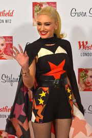 Gwen Stefani attended the Westfield London Christmas lights switch on sporting a star-themed belt, romper, and cape ensemble.