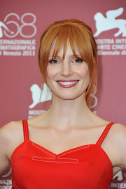 Jessica Chastain's ponytail and bangs, paired with her vivid red sundress, looked sweet and wholesome. To duplicate Jessica'a look simply section out bangs and a few wisps around the face. Brush the hair back and secure with a hair elastic at the back of the head. Smooth bangs forward to complete.