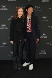 Isabelle Huppert attended the Women in Motion event wearing a black button-down shirt with crisscross detailing.