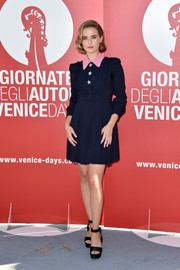 Zoey Deutch went for a vintage feel with this navy Miu Miu shirtdress, featuring a ruffle bodice, star buttons, and a contrasting pink collar, during the Venice Film Fest photocall for 'Women's Tales.'