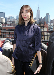 Gia Coppola styled her outfit with an elegant black leather clutch with gold trim.