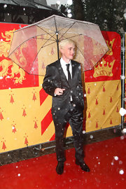 Tom Felton tries to stay dry with this see through folding umbrella.  Good luck!