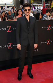 Adam Lambert traded in the glitzy glam rock style for a sleek all-black two-piece suit.