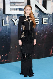 Sophie Turner paired her sexy top with a tassled black maxi skirt, also by Balmain.