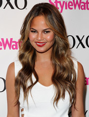 Chrissy Teigen swiped on some rich red lipstick for a shock of color to her white outfit.