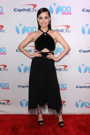 Sofia Carson complemented her dress with black ankle-strap platform sandals.