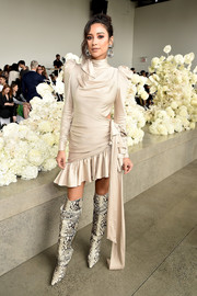Shay Mitchell sealed off her eye-catching attire with a pair of over-the-knee snake boots.