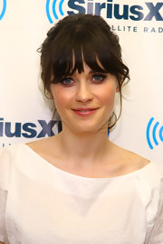 Zooey Deschanel wore her hair in a casual updo at SiriusXM Studios. Her look can be recreated by sectioning out a few face-framing strands and then loosely pinning hair in a messy bun at the nape of the neck.