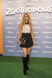 Shakira toughened up her cute dress with a pair of black knee-high boots.