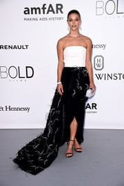 Nina Agdal attended the amfAR Cinema Against AIDS Gala wearing a strapless black-and-white gown with feather embellishments and a long train.