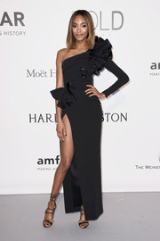 Jourdan Dunn cut a flirty figure at the amfAR Cinema Against AIDS Gala in a black Dsquared2 one-sleeve gown with ruffle detailing and a hip-high slit.