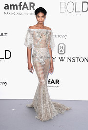Chanel Iman stole the spotlight at the amfAR Cinema Against AIDS Gala in a sheer silver net dress by Marchesa, featuring an off-the-shoulder, mermaid silhouette and strategically placed flower embellishments.