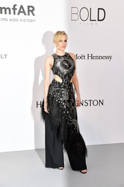 Diane Kruger was edgy-glam in a beaded and feathered cutout dress by Alexander McQueen, which she layered over matching wide-leg trousers for a more interesting finish, at the amfAR Gala Cannes 2017.