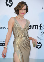 Milla Jovovich matched her champagne lamé dress with a metallic gold box clutch.