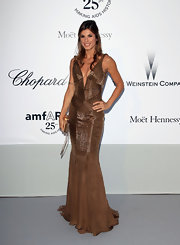 Fresh from a photoshoot onboard a yacht, Elisabetta Canalis was red carpet-ready at the amfAR gala in a beautiful bronze Cavalli gown evocative of croc skin. The deep plunging neckline and fitted silhouette perfectly highlight Elisabetta's assets; she finished the look with a loosely curled half-up hairstyle.