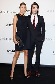 Bianca Balti held tight to her oversized black metallic clutch with gold detailing at the amfAR Milano 2012.
