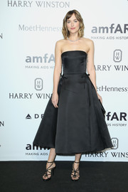 Dakota Johnson was pure elegance at the amfAR Milano 2015 in a strapless, fit-and-flare Dior LBD adorned with delicate bows on the waist.