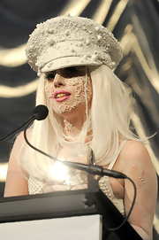 Lady Gaga showed off a pearl embellished captains hat while attending the amfar New York gala.