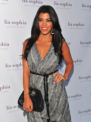 Kourtney Kardashian wore a black and white halter dress to the Lia Sophia event in Hollywood. She wore bold earrings by the designer to finish off her flirty look.
