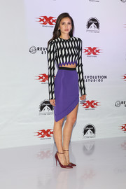 Nina Dobrev styled her outfit with a pair of red ankle-strap pumps by Jimmy Choo.