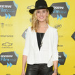 Maggie Grace's wide-brimmed fedora, white blazer, and leather pants.