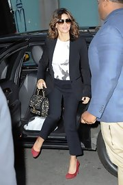 A pair of classic red pumps added a dose of color to Gina Gershon's neutral  outfit