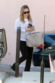 Hilary Duff complemented her black-and-white ensemble with a neutral cream-colored satchel.