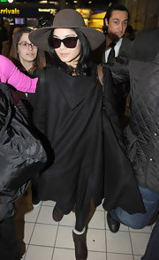 Vanessa Hudgens opted for an asymmetrical funnel neck coat while flying to Paris.