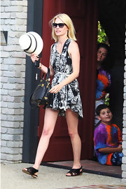 January looked spring-chic in a printed day dress with flat sandals and a striped, straw hat.