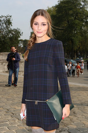 Olivia Palermo accessorized with a no-frills green leather clutch when she attended the Carven fashion show.