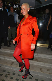 Amber dons a bold red ensemble for London Fashion Week, wearing an iridescent evening coat.