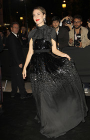 Ulyana Sergeenko made an elegant entrance to the 'Mademoiselle C' premiere in a high-neck black pin-dot gown with a beaded midsection.