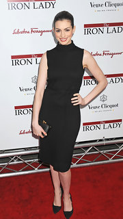Anne Hathaway maintained her monochromatic style with a sleek black box clutch with gold trim.