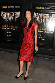 Demi Moore topped off her chic red printed dress with black pumps complete with studded detailing on the heel.