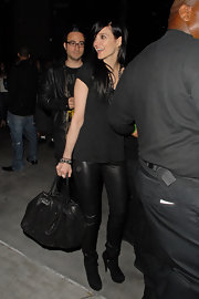 Ashlee toted a soft-sided black leather, double strapped handbag. The scrunchy, worn accessory complemented her edgy black ensemble.