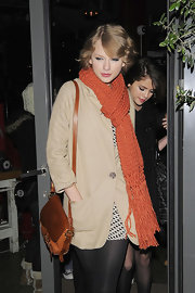 Taylor Swift looked warm and cozy in her burnt orange knit scarf. Pinned up ringlets completed her look.