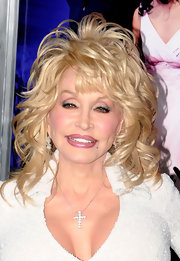 Dolly accessorized her sparkling outfit with a diamond pendant cross.