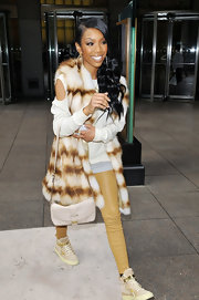 Brandy finished off her leather look with a long fur vest in NYC.