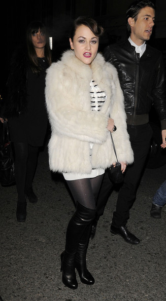 Jamie wears a thick white fur coat with black boots and tights to the Dior party in London.