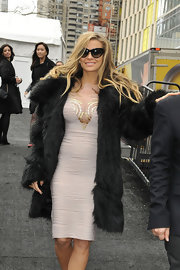 Carmen Electra showed her love of all things glamorous with a fitted cocktail dress, cat eye sunglasses and large fur coat.