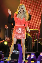 Carrie Underwood accessorized her striking coral ensemble with layered necklaces.
