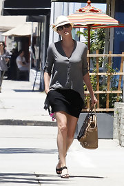 Charlize sported a light gray cardigan with her mini skirt.