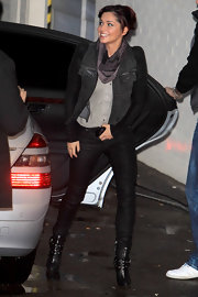 Cheryl Cole stays on trend in black ankle boots. The heels are wrapped in rivet embellished buckles.