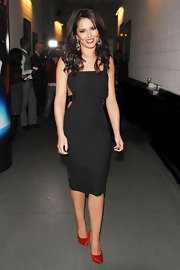 Cheryl puts the edge on the little black dress in a sexy leather strapped number in London.