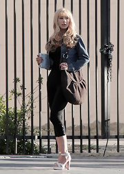 "On the set off her new movie ""Burlesque"" Christina Aguilera donned a brown suede hobo bag. She toned down her look with a pair of leggings and a jean jacket."