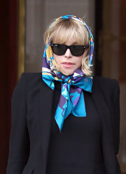Courtney wrapped her printed scarf around her head while leaving her London hotel.