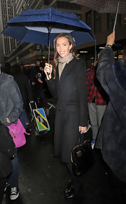 Olivia Chantacaille kept warm and dry in a long black wool coat.